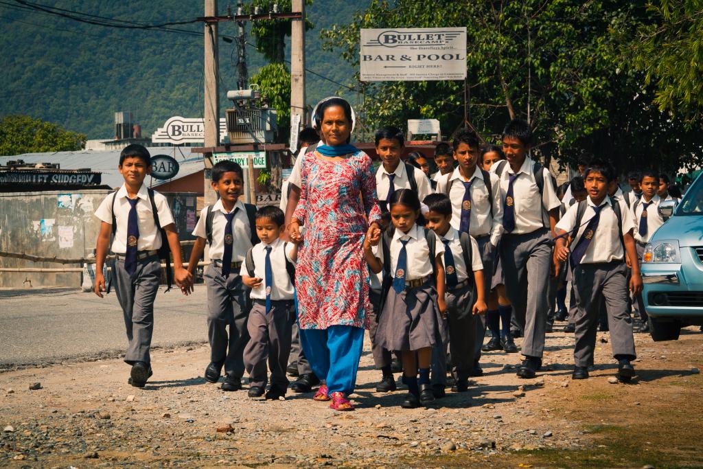 En lärare på promenad med sin skolklass.