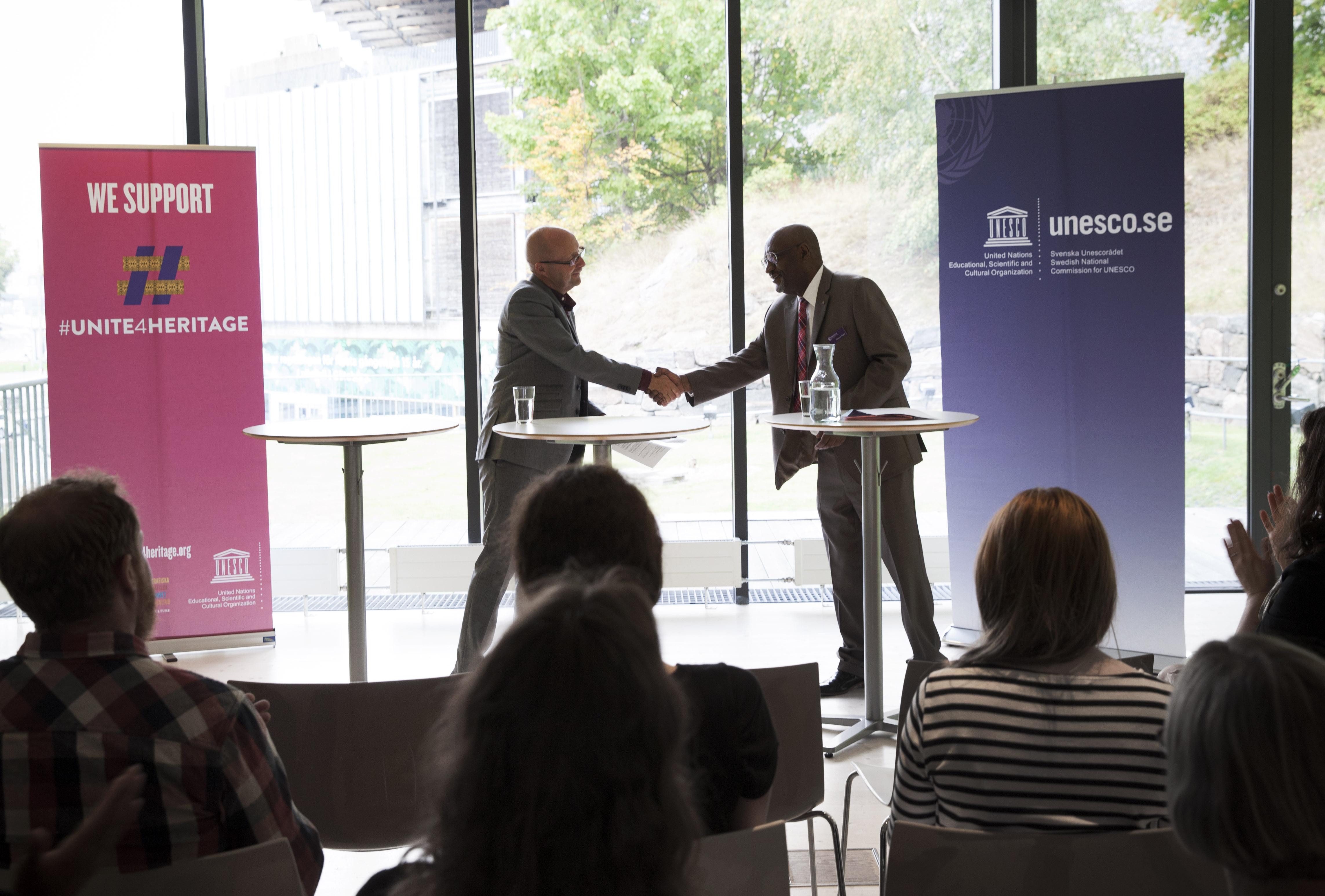 Unescos vice generaldirektör Getachew Engida överräcker dokumentet som visar att Världskulturmuseerna stödjer Unescos kampanj #Unite4Heritage.
